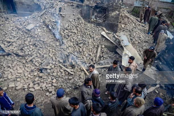 People are seen gathered at the damaged house after the gun battle Indian troops laid a siege around an area in Tral which is some 60 Kms from...