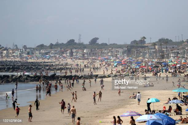 People are seen gathering on the beach north of Newport Beach Pier on April 25 2020 in Newport Beach California Southern California is expecting...
