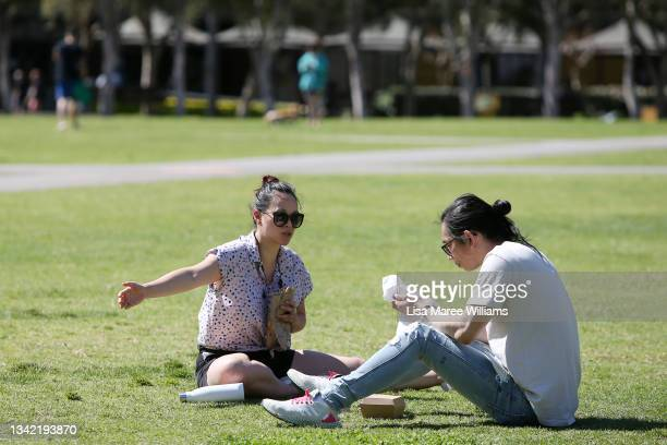 People are seen having a picnic lunch at Tumbalong Park in the Darling Harbour precinct on September 24, 2021 in Sydney, Australia. COVID-19...