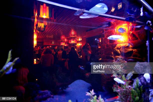 People are seen in a bar through a fish tank in Paris France on November 25 2017
