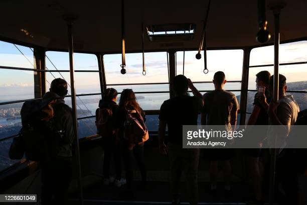 People are seen in a cable car as they watch the view of Grouse Mountain in Vancouver, British Columbia, Canada on June 12, 2020. Grouse Mountain...
