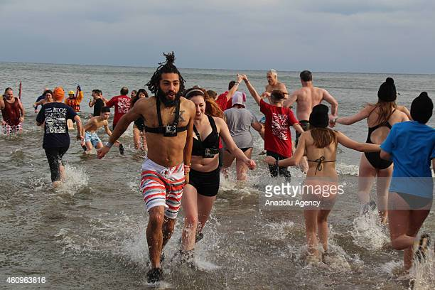 People are seen in a lake at temperatures around 18 centigrade degrees during the 30th annual Polar Bear Dip in the suburban town of Oakville near...