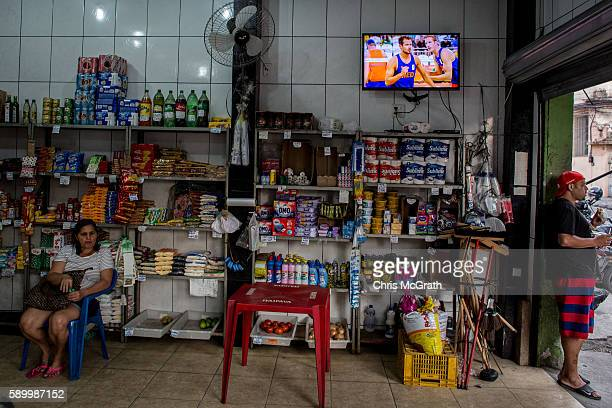 People are seen in a small neighbourhood grocery store as the Olympic games is shown on a tv screen on the outskirts of a 'favela' community on...