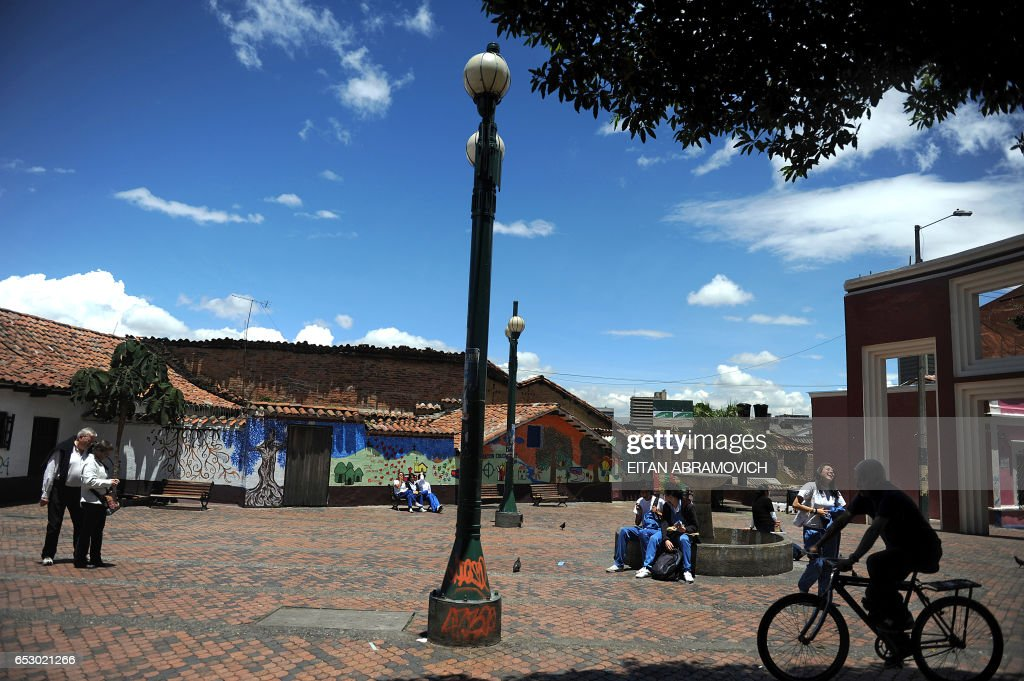 People are seen in El Chorro de Quevedo square in the historic neighborhood of La Candelaria in Bogota on September 17, 2009. La Candelaria is Bogota's oldest neighbourhood and the city's historical center, known for its colonial houses with wooden balconies and clay shingle roofs. AFP PHOTO/Eitan Abramovich /