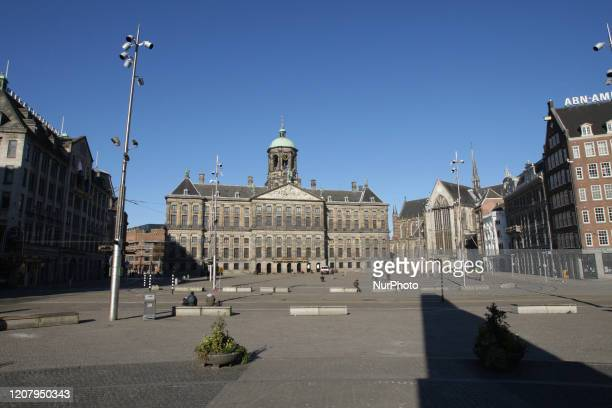 People are seen in front of the Royal Palace on an empty Dam Square on March 22, 2020 in Amsterdam,Netherlands.The Dutch government ordered all Dutch...