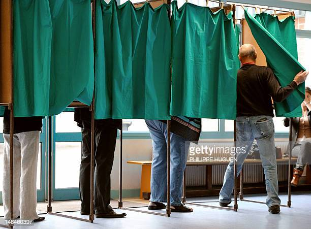 People are seen in polling booths during the second round of the French parliamentary elections on June 17 2012 at a polling station in HeninBeaumont...