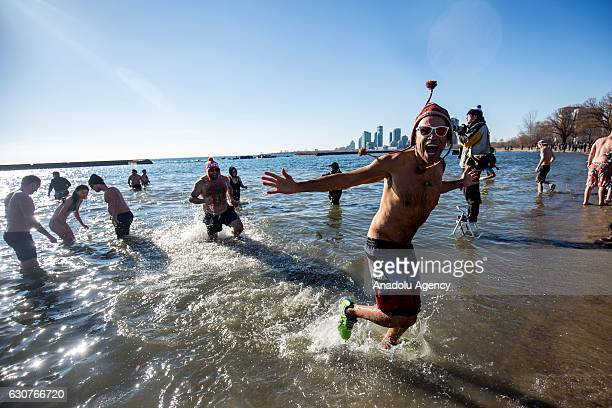 People are seen in the frigid waters of Lake Ontario at Sunnyside beach during the Toronto Polar Bear Dip in Toronto Canada on January 01 2017...