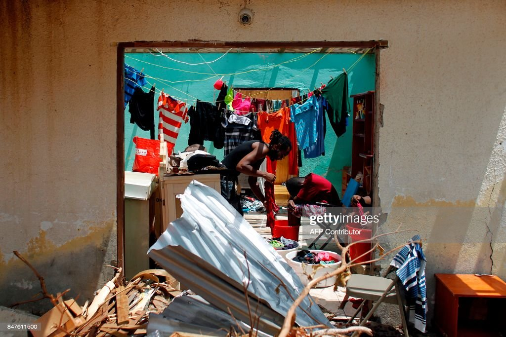 TOPSHOT - People are seen inside a wrecked house days after this Caribbean island sustained extensive damage in the wake of Hurricane Irma, Friday, September 15, 2017 in St. Martin. / AFP PHOTO / Ricardo ARDUENGO