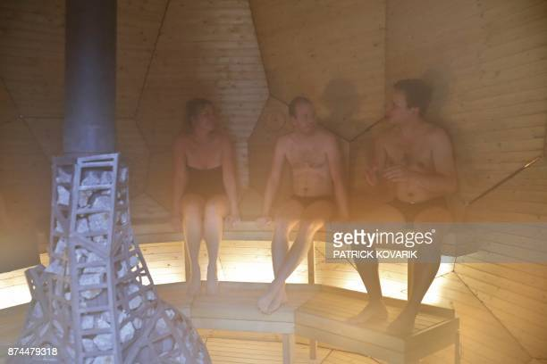 People are seen inside the eggshaped sauna 'solar egg' designed by Swedish artists Lars Bergström and Mats Bigert in the courtyard of the Swedish...