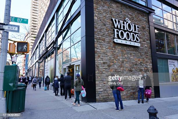 People are seen lined up in front of Whole Foods during the coronavirus pandemic on April 15, 2020 in New York City. Grocery stores across the...