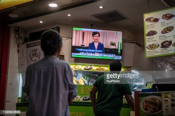 People are seen looking at a television scream which is displaying a news broadcast of Hong Kong Chief Executive Carrie Lam in Hong Kong on September...