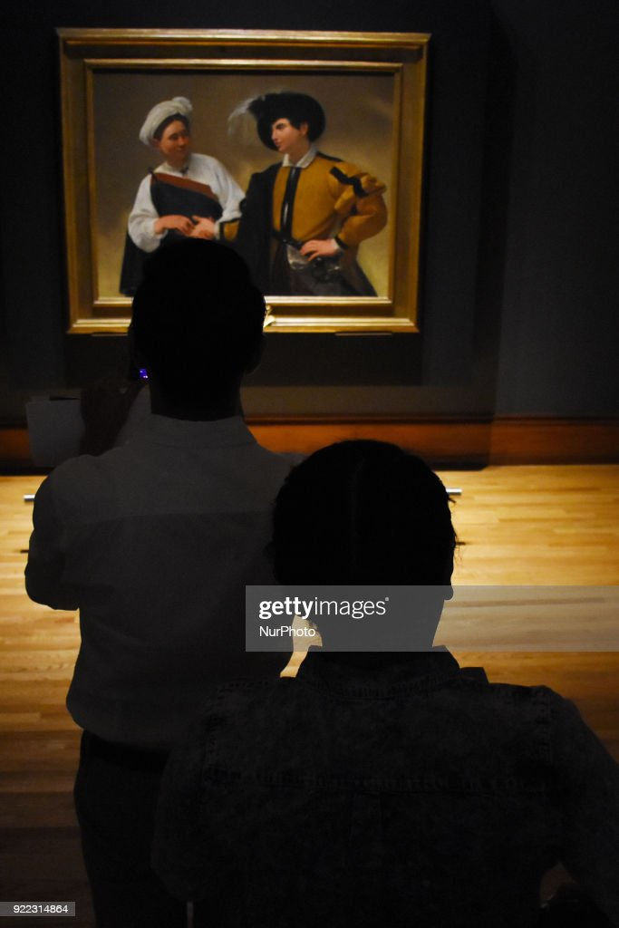 people are seen looking at the artwork La Buenaventura (1596) painted in oil on canvas by the Italian artist Caravaggio (1571-1610) at the Exhibition 'Caravaggio an art, a gift' at National Museum of Art on February 21, 2018 in Mexico City, Mexico