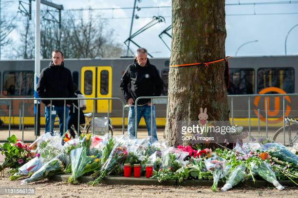 People are seen looking at the memorial site while a tram is passing on the background. The day after three people were killed and five injured...