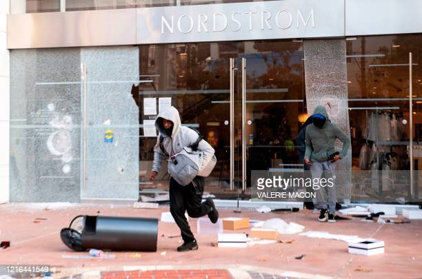People are seen looting stores at the Grove shopping center in the Fairfax District of Los Angeles on May 30 2020 following a protest against the...