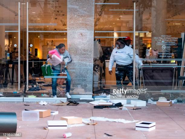 People are seen looting stores at the Grove shopping center in the Fairfax District of Los Angeles on May 30, 2020 following a protest against the...