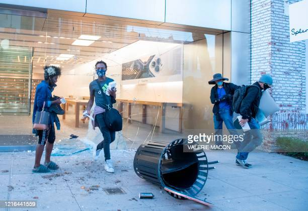 People are seen looting the Apple store at the Grove shopping center in the Fairfax District of Los Angeles on May 30, 2020 following a protest...