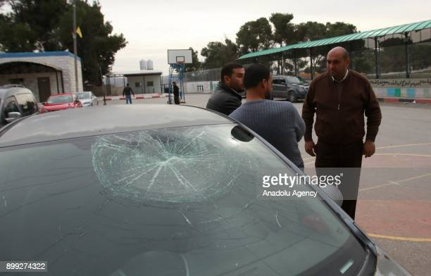 People are seen near a car damaged by Jewish settlers belonging to school management after Jewish settlers stormed a Palestinian school in Nablus...