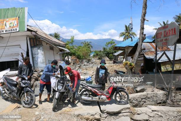People are seen near destroyed buildings after an earthquake measuring 7.7 SR and the tsunami wave, in south of Palu, Sigi, Central Sulawesi,...