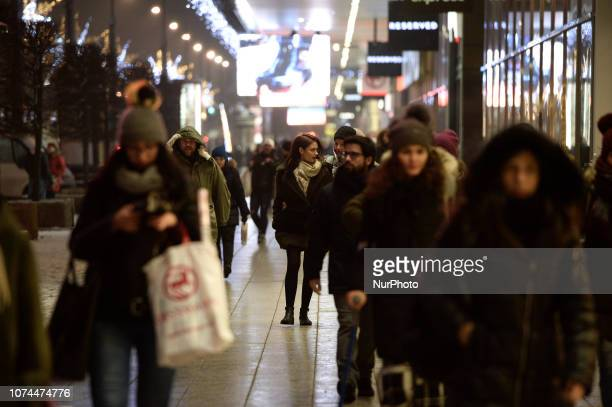 People are seen near shops on Marszalkowska street in the center of Warsaw Poland on December 20 2018 Poles this year will spend on average 6 percent...