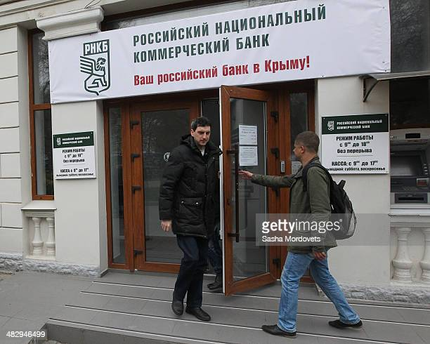 People are seen near the entrance of a newly opened branch of Russian National Commercial Bank on April 5, 2014 in Sevastopol, in the disputed...