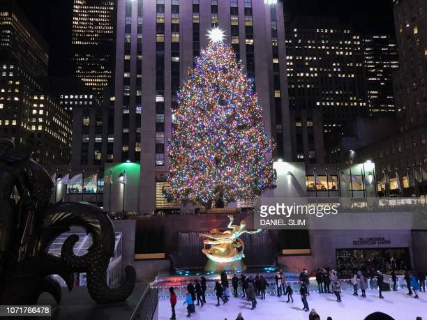 People are seen near the Rockefeller Center Christmas Tree a worldwide symbol of the holidays in New York City on December 10 2018
