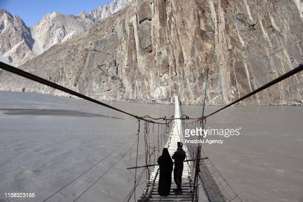 People are seen on a wooden bridge with mountain views on the Karimabad Region, where a number of summits meet and host historical Baltit Fort, also...