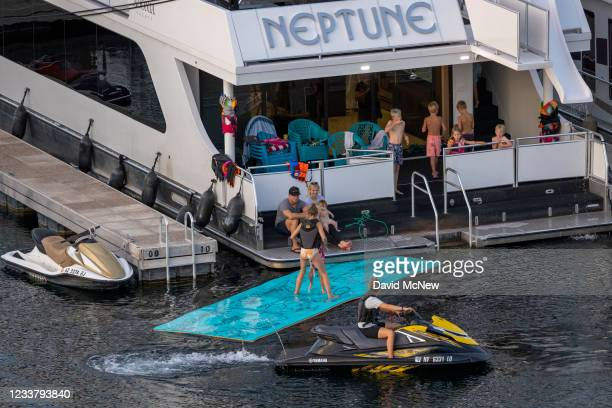 People are seen on boats at the Antelope Point Marina, where the launch has been closed because of record low water levels, that float lower than...