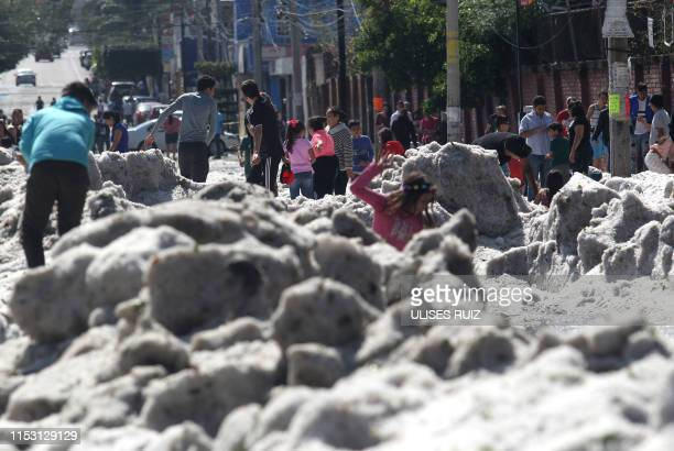 People are seen on June 30, 2019 in a street of Guadalajara, Jalisco State, Mexico, after a hail storm fell in the area. - A freak hail storm on...