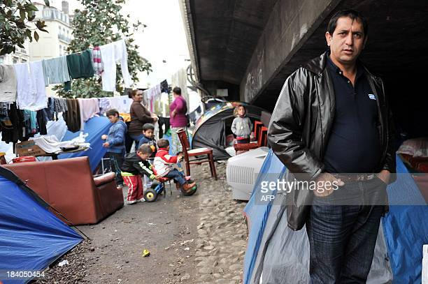 People are seen on October 11 2013 in a campsite of Albanian asylum seekers located under the Kitchener bridge near the Perrache train station in...