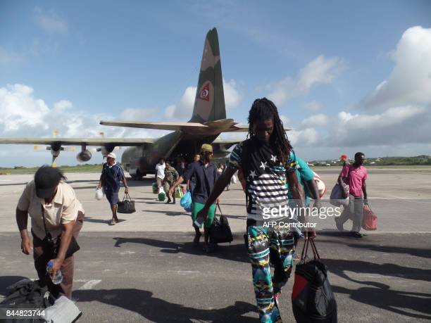 People are seen on September 8 2017 in VC Bird International Airport Antigua devastated by Hurricane Irma Hurricane Irma on Thursday slashed its way...