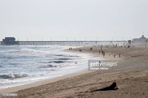 People are seen on the Balboa Peninsula Beach on April 11 2020 in Newport Beach California Many beaches and public spaces across California have been...