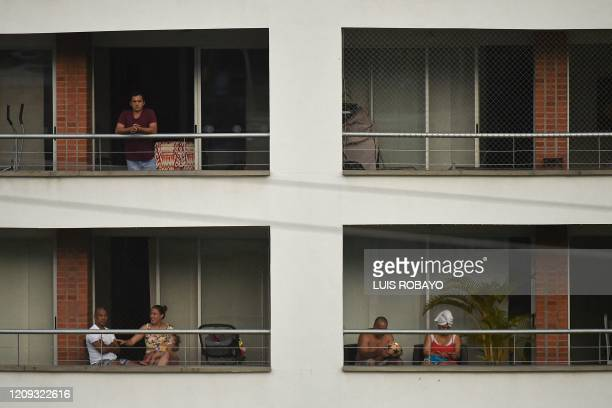 People are seen on the balconies for their apartments in Cali, Colombia, on April 6, 2020 during the lockdown ordered by the government to slow the...