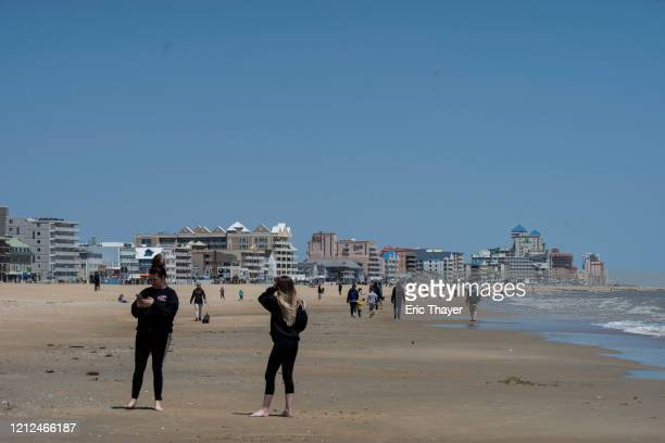 People are seen on the beach as the area reopens from the coronavirus pandemic on May 10 2020 in Ocean City Maryland A popular summer tourist...