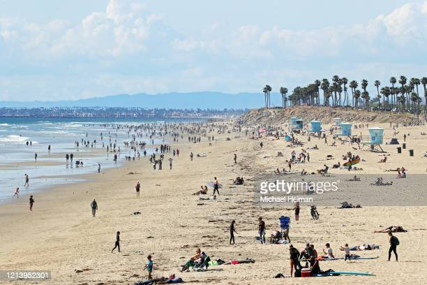 People are seen on the beach on March 21 2020 in Huntington Beach California California Governor Gavin Newsom issued a statewide 'stay at home' order...