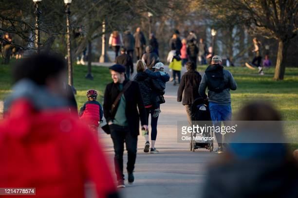 People are seen out walking in Primrose Hill on March 25, 2020 in London, United Kingdom. British Prime Minister, Boris Johnson, announced strict...