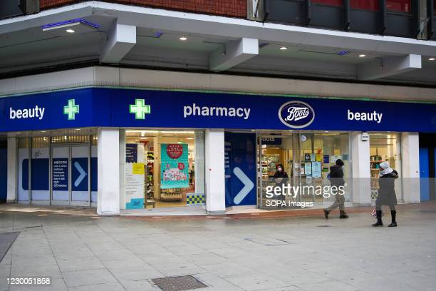 People are seen outside a branch of Boots store in London, UK.
