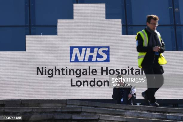 People are seen outside the NHS Nightingale Hospital London created in the ExCeL London exhibition centre in London on April 1 to help with the novel...