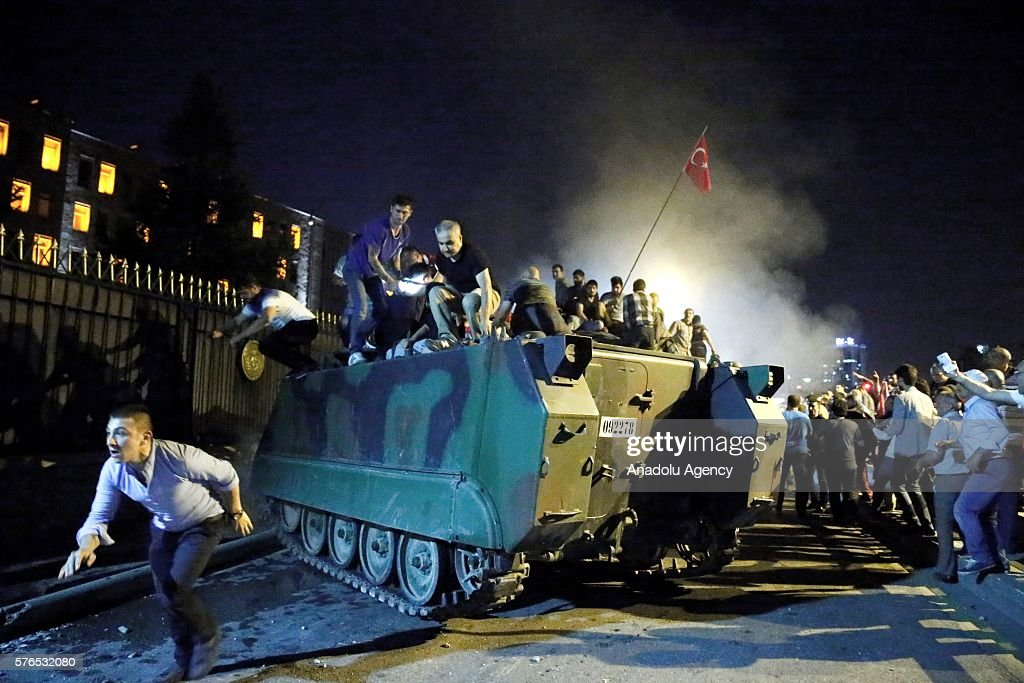 People are seen over an armored vehicle as they gather to react against military coup attempt, in Ankara, Turkey on July 16, 2016.