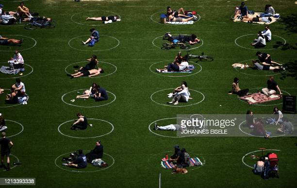 People are seen practising social distancing in white circles in Domino Park, during the Covid-19 pandemic on May 17, 2020 the in Brooklyn borough of...