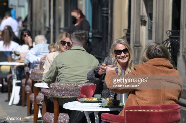 People are seen raising their glasses as pubs with outdoor facilities reopen on April 30, 2021 in Belfast, Northern Ireland. Non essential retail...
