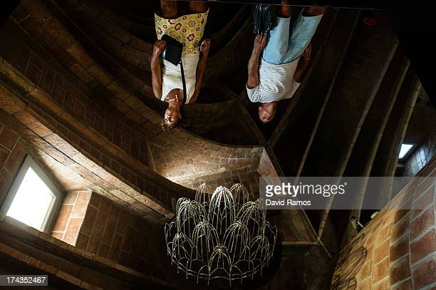 People are seen reflected in a mirror as they visit the museum of Antoni Gaudi's building 'La Pedrera' or 'Casa Mila' on July 24 2013 in Barcelona...