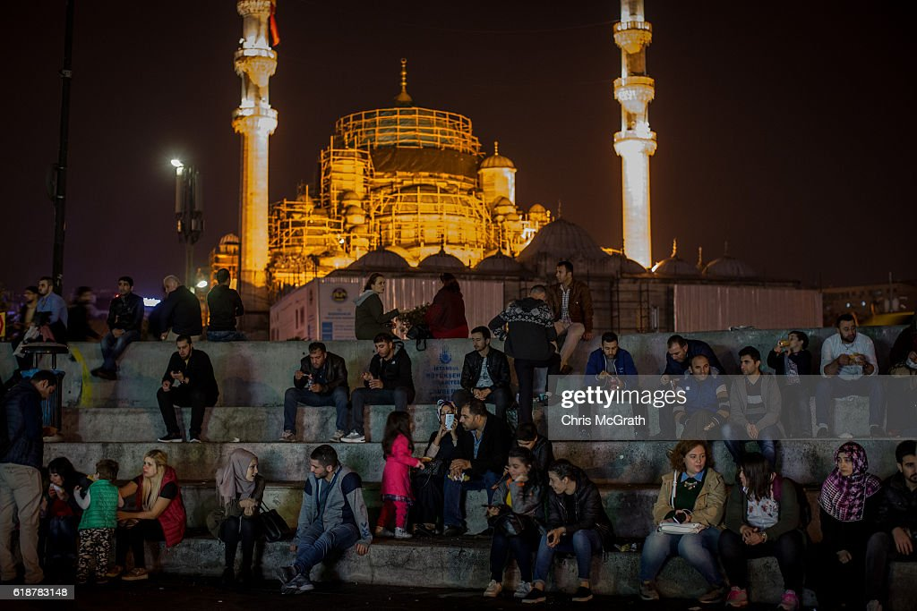People are seen relaxing in Eminonu in front of the Yeni Mosque under renovation on October 22, 2016 in Istanbul, Turkey. Since the failed coup attempt on July 15, 2016 which saw 240 people killed including 173 civilians, Turkish authorities initiated a state of emergency, leading to an unprecedented crackdown on individuals and organizations with links to US-based cleric Fethullah Gulen and his organization blamed for instigating the uprising. The purge, targeting teachers, journalists, soldiers, judges, academics, police, military leaders, schools and universities has so far seen approximately 100,000 people dismissed, 70,000 detained, 32,000 arrested, 130 media outlets closed and some 15 universities shuttered. The failed coup and subsequent purge only appears to have further bolstered the president's popularity and increased nationalism across the country with July 15th having been marked as a new national holiday. Turkish flags, already prominently displaying all over have increased in numbers, as well as posters of those killed fighting the coup plotters appearing in train stations and public squares. The Bosphorus Bridge in Istanbul, which saw heavy fighting during the coup has been renamed the '15th July Martyr's Bridge'. These changes, follow a year of instability in the country with constant terrorist attacks, an economic downturn, plummeting tourism, and a refugee crisis, all contributing to Turkish society undergoing its most dramatic restructuring in decades.