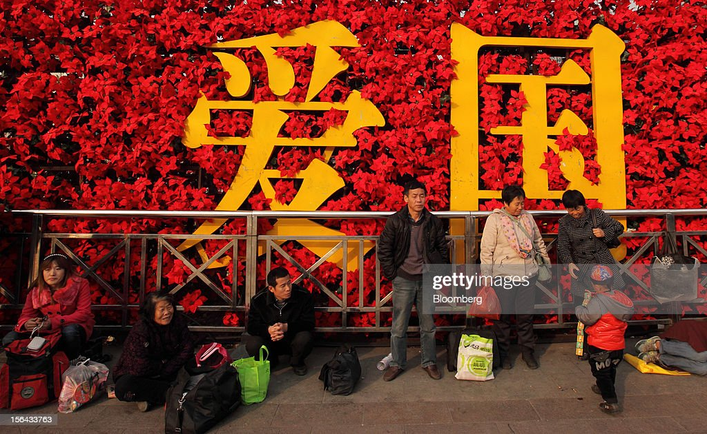 People are seen resting in front of a floral flower display which reads 'patriotism' in Chinese characters in Beijing, China, on Thursday, Nov. 15, 2012. Xi Jinping replaced Hu Jintao as head of the Chinese Communist Party and the nation's military, ushering in the fifth generation of leaders who are set to run the world's second-biggest economy over the next decade. Photographer: Tomohiro Ohsumi/Bloomberg via Getty Images
