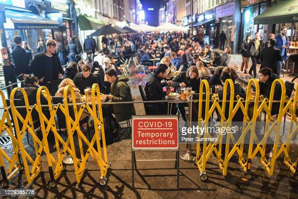 People are seen sat outside bars and restaurants in Soho during Halloween celebrations on October 31, 2020 in London, England. Earlier today, Sat,...