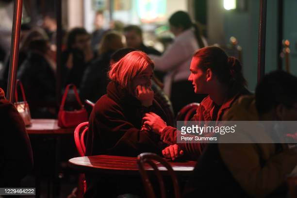 People are seen sitting at tables outside a restaurant in Soho on November 4, 2020 in London, England. Non-essential businesses, including pubs and...
