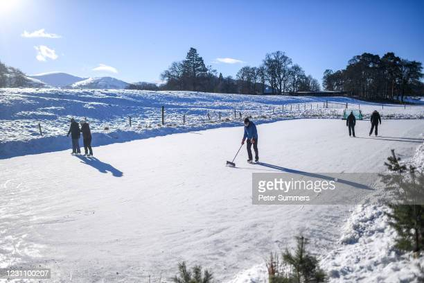 People are seen skating on a frozen pond which has been turned in to an ice rink on February 11, 2021 in Aviemore, United Kingdom. The village of...