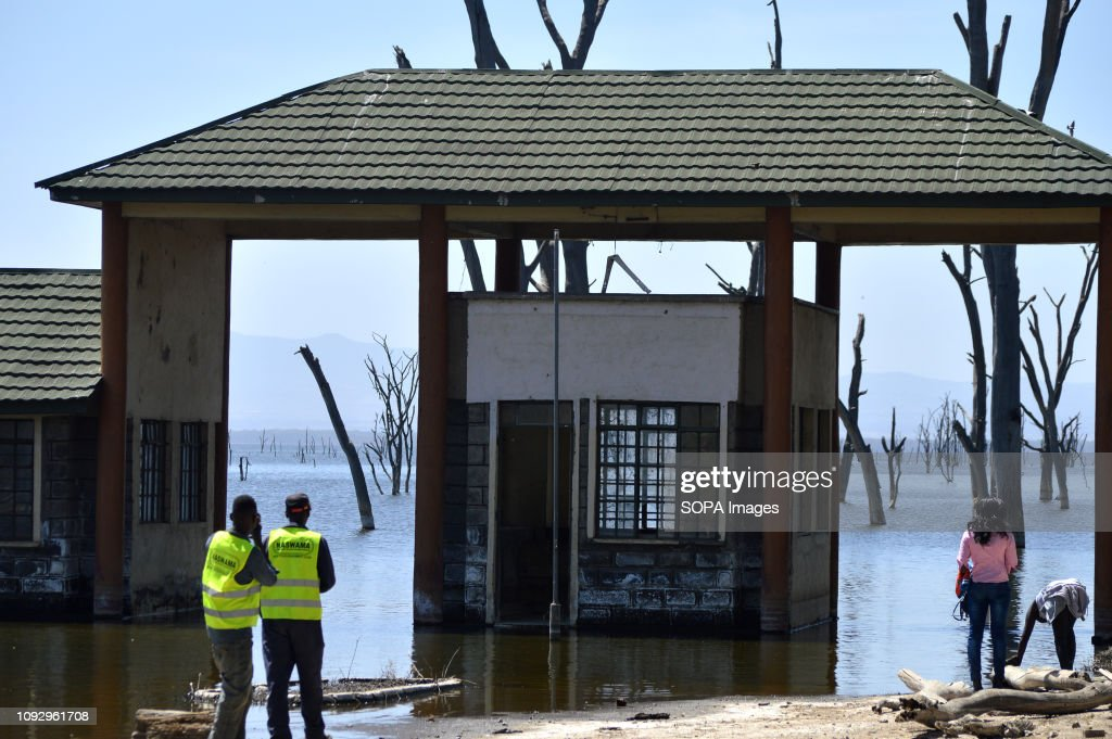 People are seen standing in front of a submerged office... : News Photo