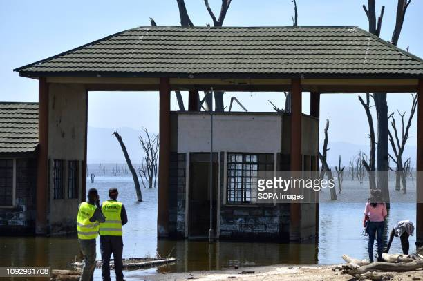 PARK NAKURU RIFTVALLEY KENYA People are seen standing in front of a submerged office buildings from the rising water levels in the lake during the...