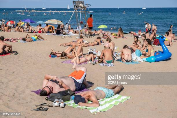 People are seen sunbathing at the Barceloneta beach during the coronavirus crisis. The city of Barcelona faces new outbreaks of coronavirus cases...