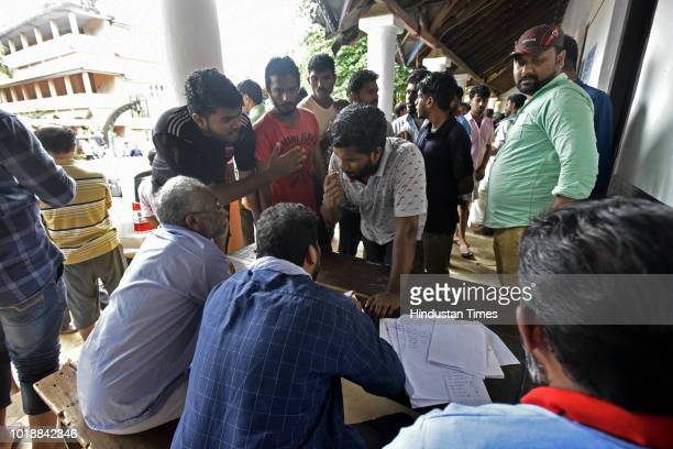 People are seen taking information about their relatives at a rescue camp in a school at Panadala on August 18 2018 in district Pathanamthitta India...